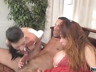 Two busty gorgeous brunettes sucking one stiff cum shooter