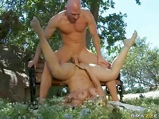 Muscled bald dude drilling breasty blonde on bench in park